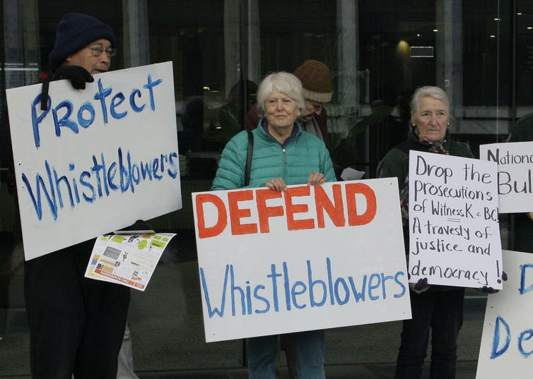Protesters hold signs saying 'defend whistleblowers'.