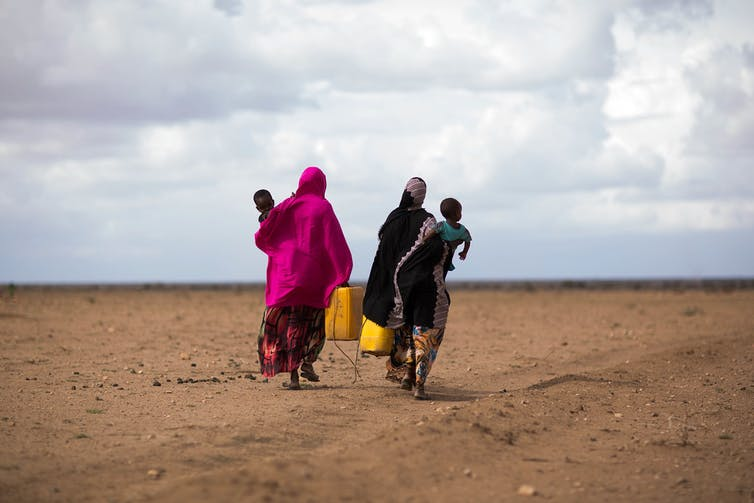 Two women carry small children and water jugs across a dry, empty landscape