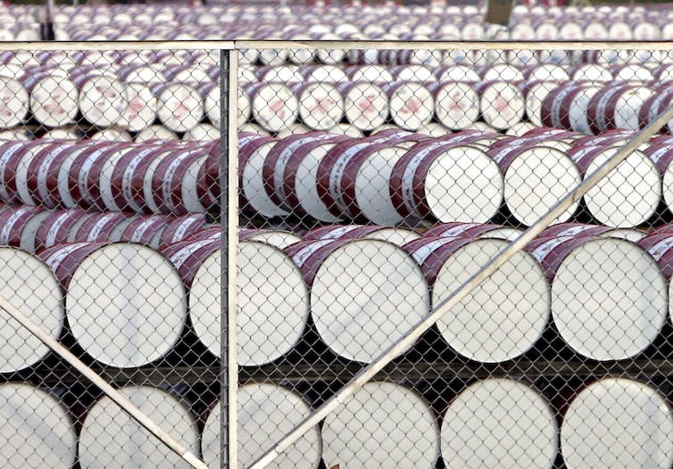 White-bottomed barrels piled in rows behind a chainlink fence.