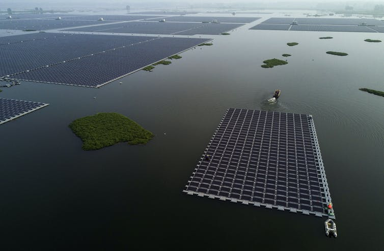 A boat pulls a large section of solar panels into place among others on the large lake.