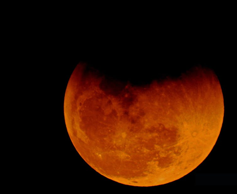A red hued moon with a shadow on the top.
