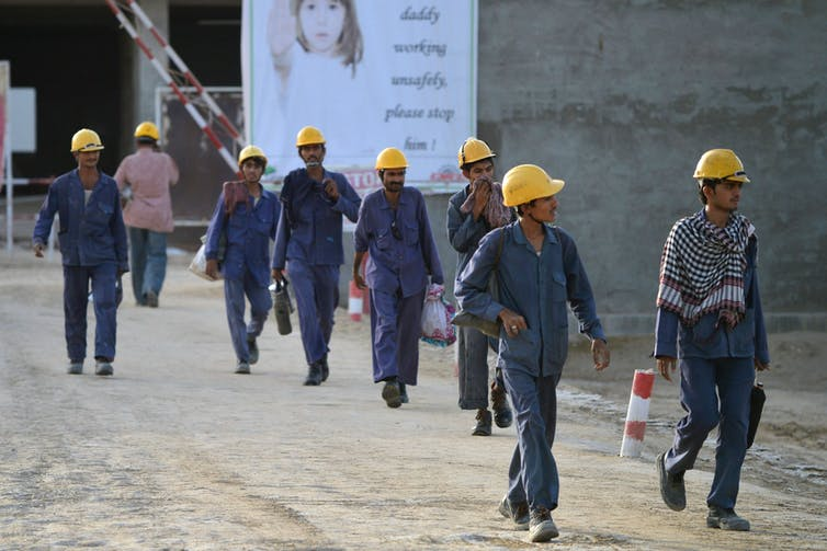 Construction workers in hard hats pass a sign urging them to work safely