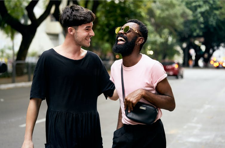 Two man laugh in the street.