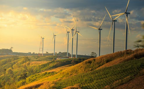 Wind turbines on a hill at sunset
