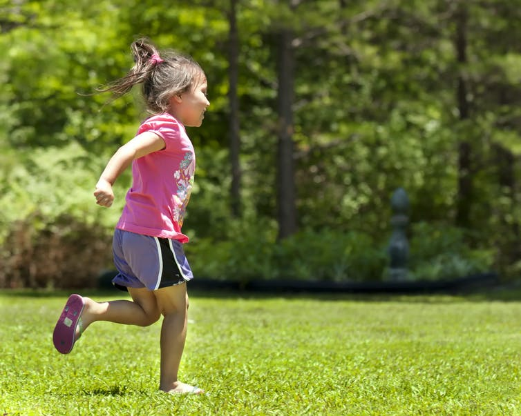 A young girl running in the park.