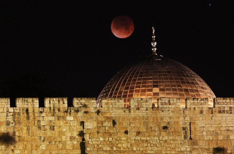 A red moon over an ancient mosque.