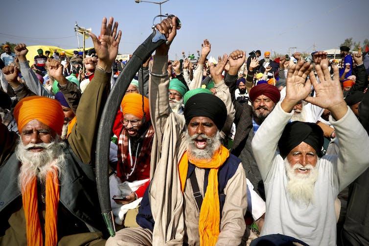 Men in colourful turbans shout