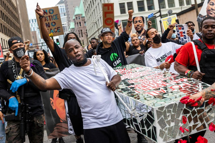 Protesters carry a cardboard coffin down a city street