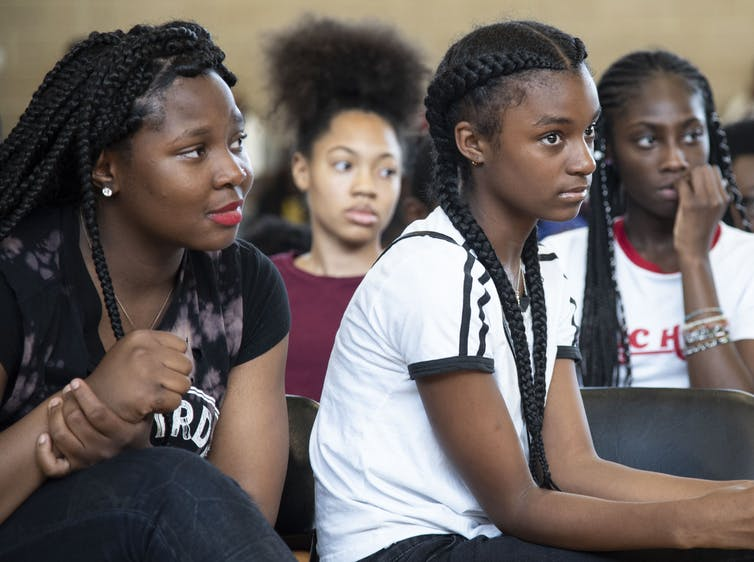 Four Black youth listen attentively