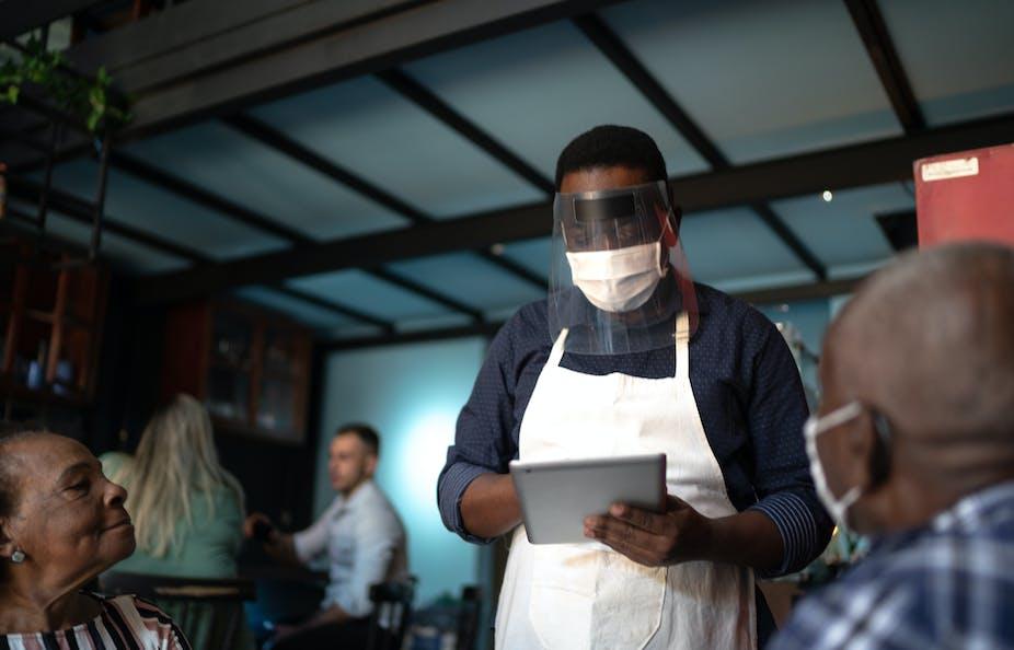 Masked waiter taking an order in a restaurant.