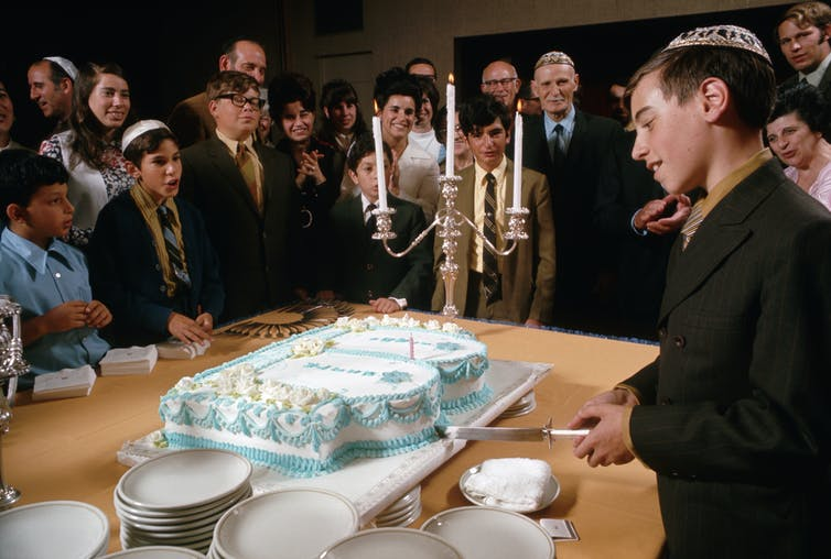 A Jewish boy cuts a cake for family and friends after his bar mitzvah ceremony.
