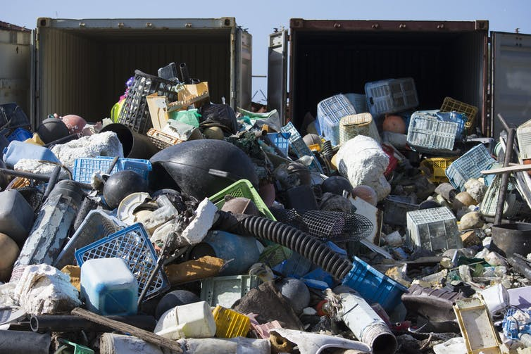 Heaps of debris spill out of shipping containers.