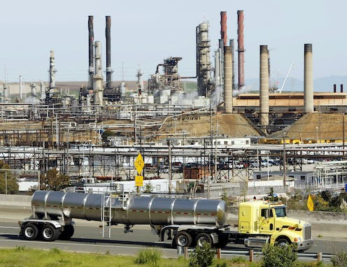 A tanker truck drives past a large refinery.