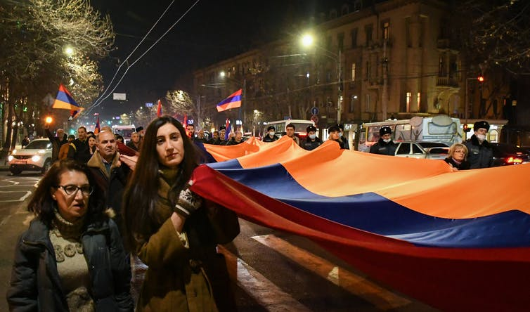 Women and men carrying a giant red, blue and orange flag through the streets at night.