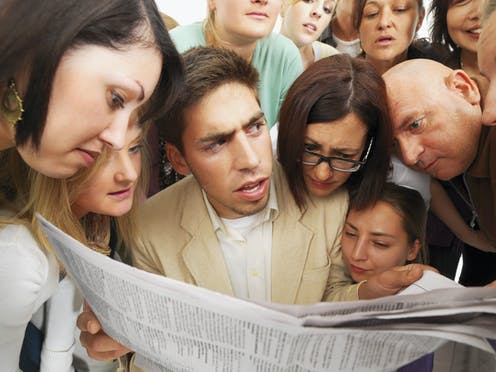 A man with an intense look on his face is holding a newspaper with a lot of people around him looking at it.
