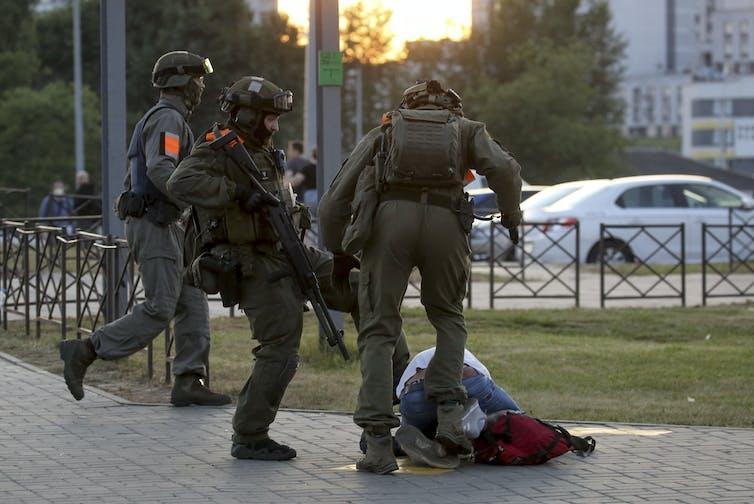 Police officers kick a demonstrator in Minsk.