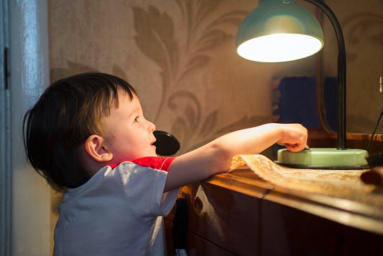 boy turns off lamp