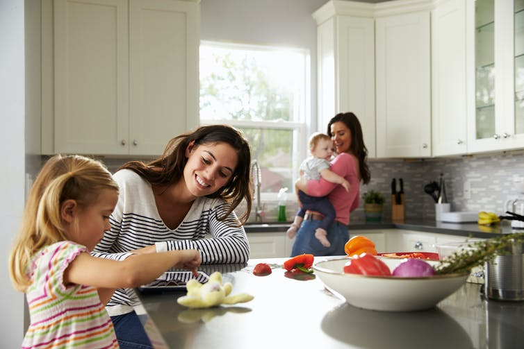 Lesbian couple with two young children in the kitchen.