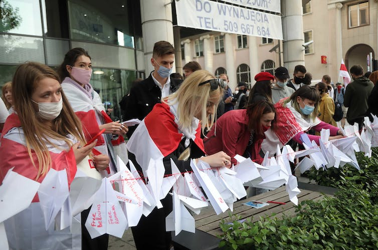 Women wearing capes made from the red and white flag of the Belarusian opposition making paper planes.