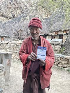 An elderly man holds up a vaccine card.