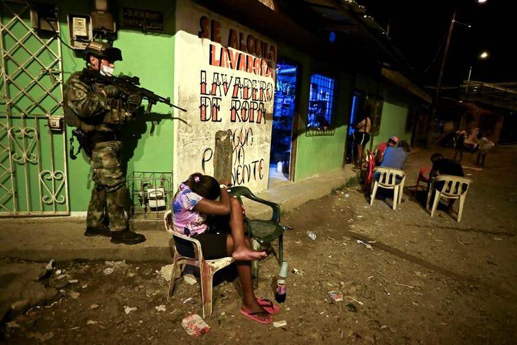 Soldier in fatigue holds a weapon while a young girl covers her head