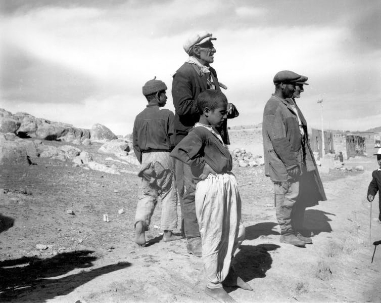 Three men and two boys stand on a dry landscape