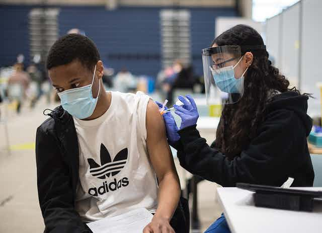 A young man in a mask is vaccinated
