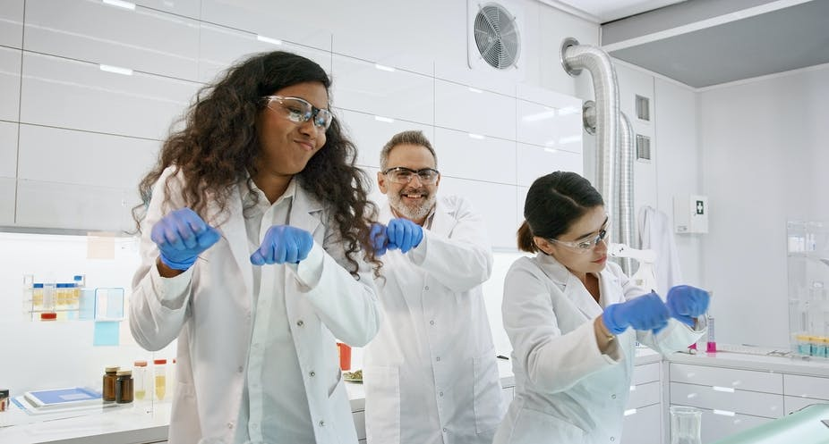 Three lab workers dancing.