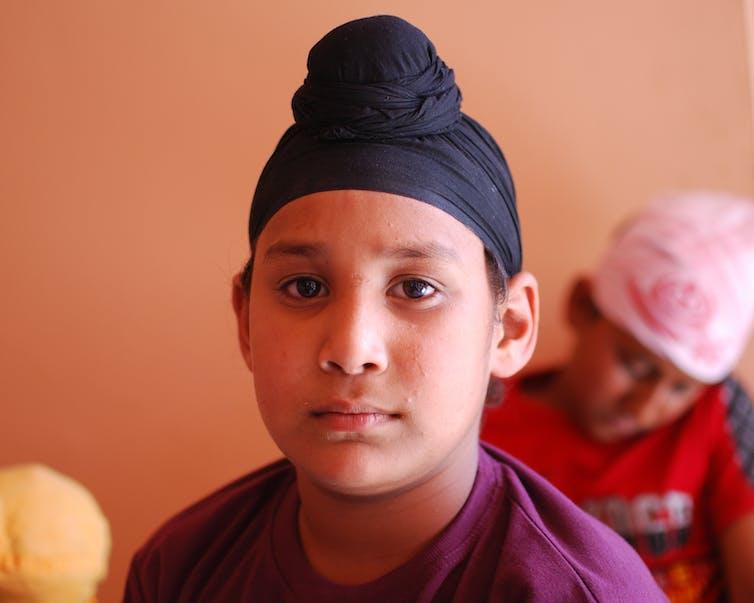 A boy wearing a patka.