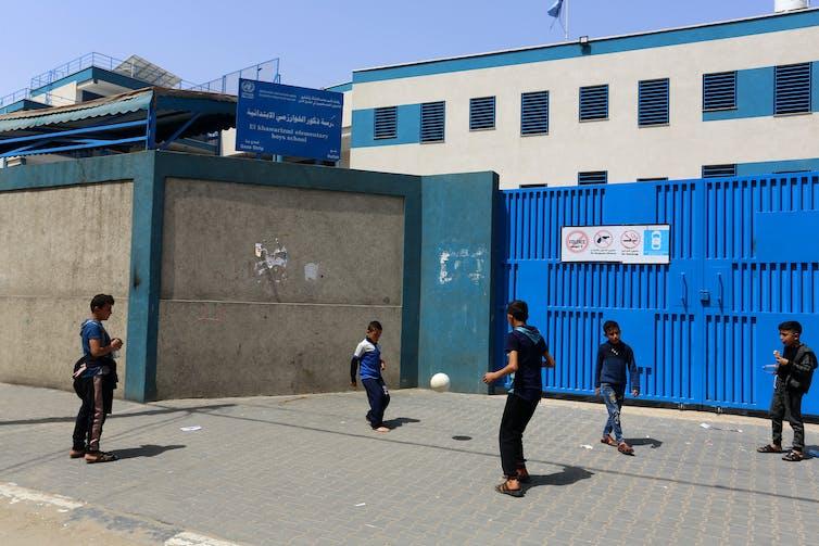 Boys playing football outside closed school gates in Gaza