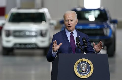 President Biden speaking in front of two electric SUVs at a factory