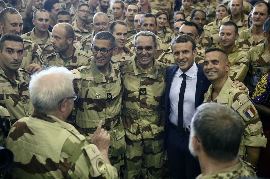 A man wearing a suit, tie and shirt poses with several soldiers in military fatigues.