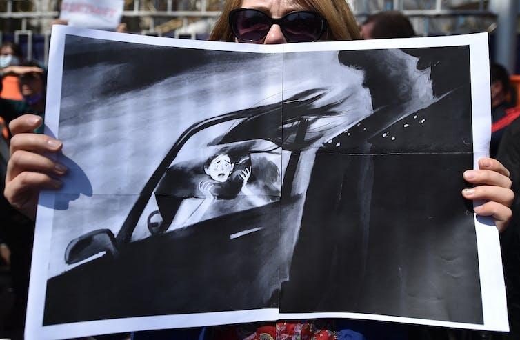 Mujer sostiene un dibujo que representa a una mujer asustada que se lleva en un automóvil