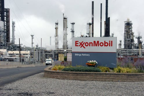 An Exxon Mobil sign sits in front of its Billings Refinery in Billings, Mont., with smoke stacks in the background.