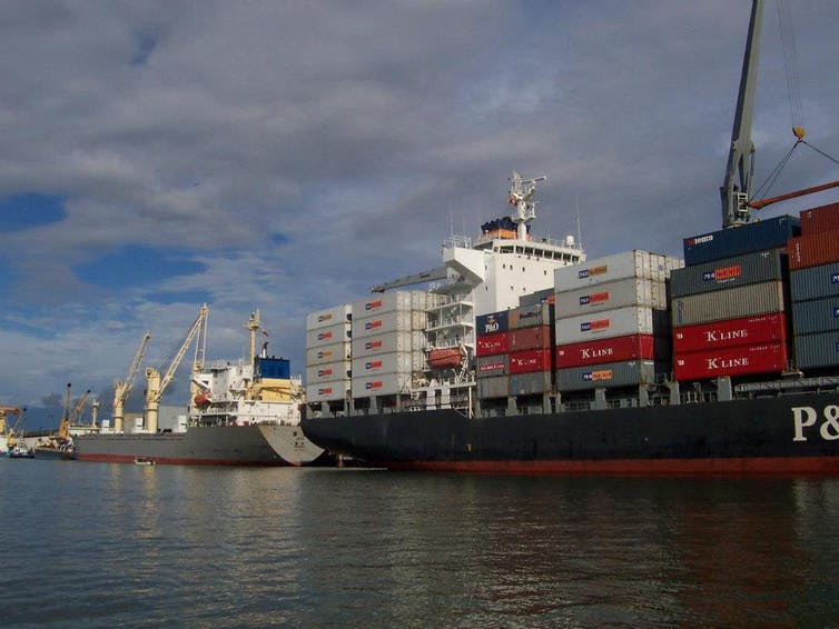Large ships with stacked containers lined up in the water