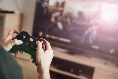 A youngster plays with a video game controller in front of a screen