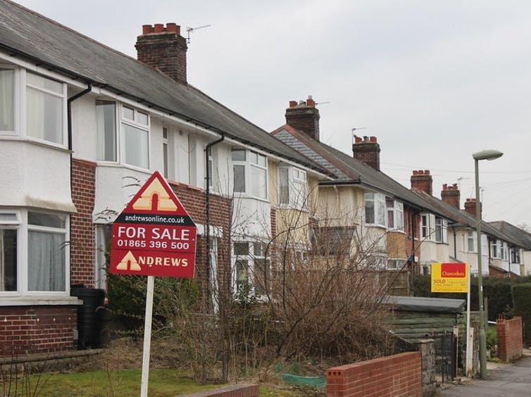 Row of houses with For Sale signs