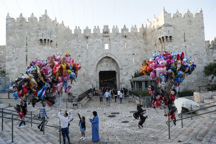 Des Palestiniens se rendent pour assister aux prières de l'Aïd al-Fitr à la mosquée Al Aqsa dans la vieille ville de Jérusalem, tandis que des enfants jouent avec des ballons dans la rue à l'extérieur, le 13 mai 2021.