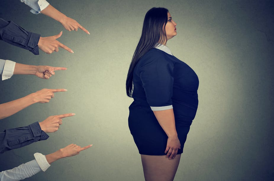 Fingers pointing at a person who is overweight.