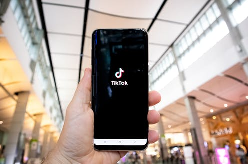 Person holding a phone with TikTok app opening