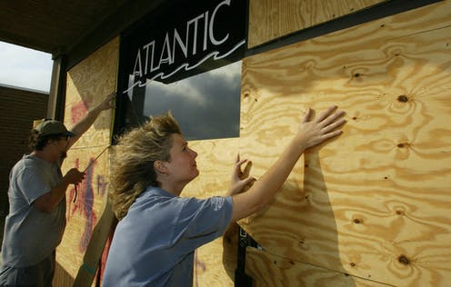 A man and woman put plywood over a store's windows