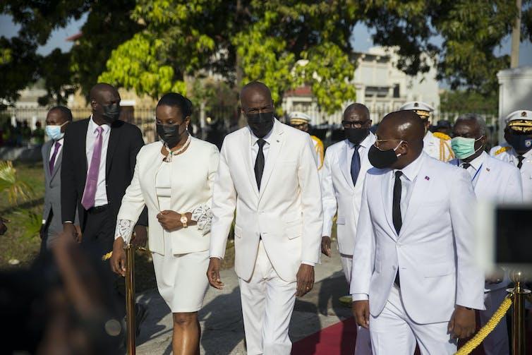 Le président haïtien Moise et son épouse marchent en compagnie d'un homme, tous vêtus de blanc
