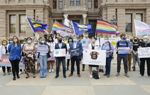 Protesters in front of a government building holding signs and flags supporting transgender rights.