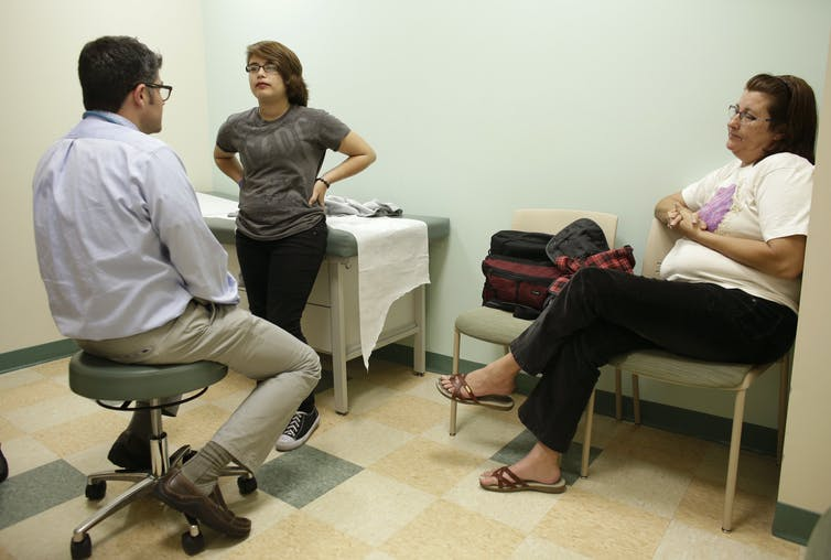 A doctor speaking with a young transgender person and their mother.