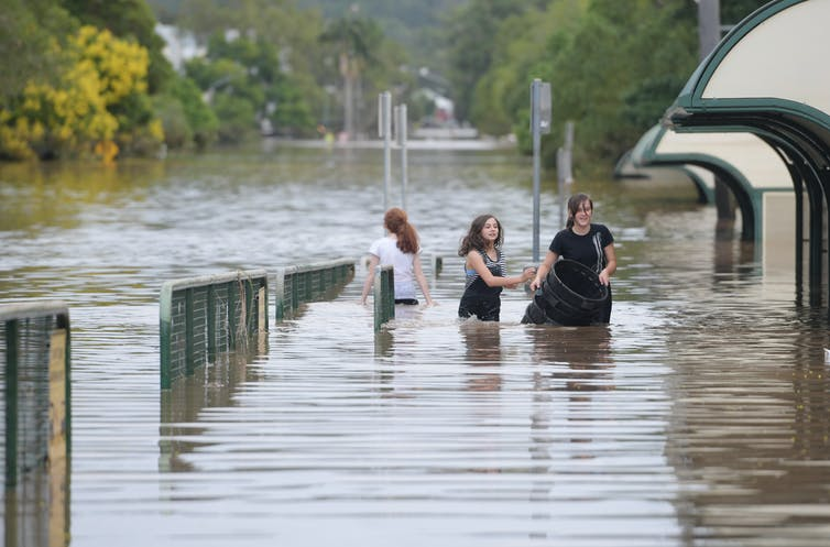 Three girls wade through floodwaters