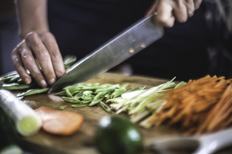 A chef cutting vegetables on a cutting board.