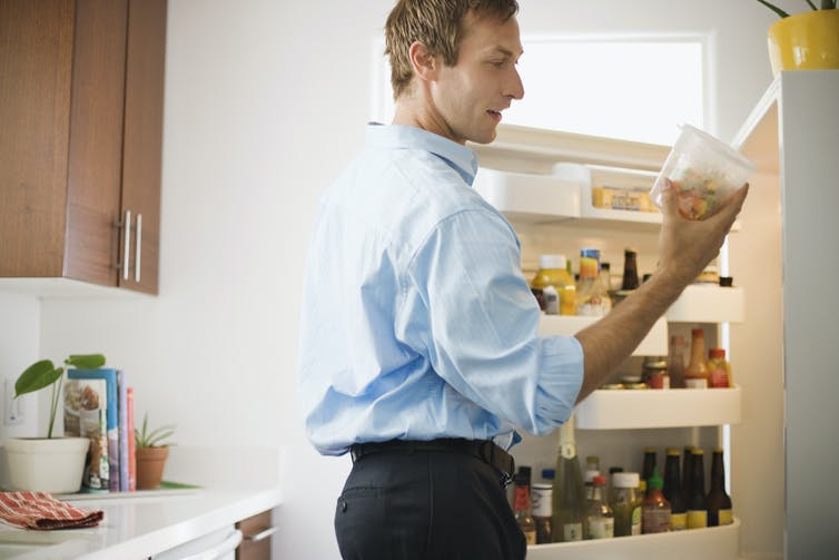 A man takes the leftovers out of the fridge.