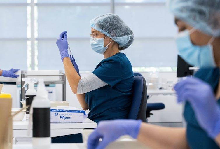 Staff preparing COVID-19 vaccines.