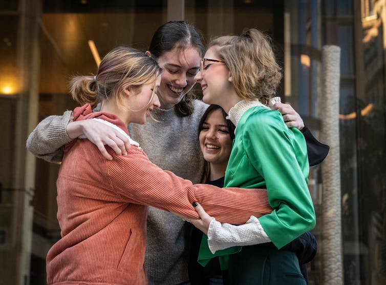 Four teenagers hugging outside the court