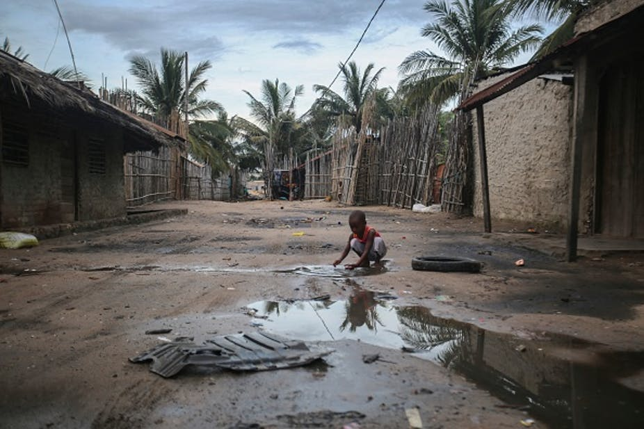 Child crouches on a muddy, puddled road between buildings, with palm trees in the background